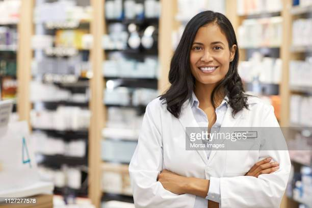portrait of pharmacist with arms crossed at store - pharmacist stock pictures, royalty-free photos & images