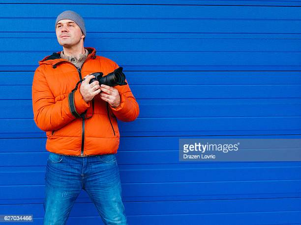 Portrait of photographer in winter, near blue background