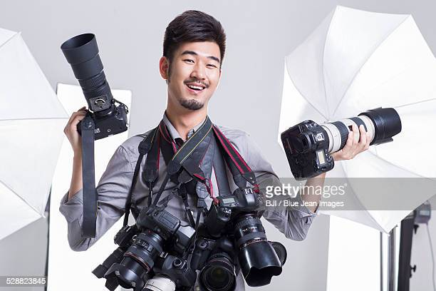 Portrait of photographer with many cameras hanging on his neck