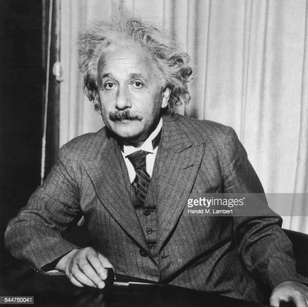 Portrait of physicist Albert Einstein, sitting at a table holding a pipe, circa 1933.