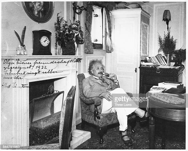 Portrait of physicist Albert Einstein sitting in an armchair and smoking a pipe, circa 1932.