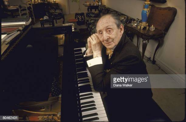 Portrait of pianist Vladimir Horowitz leaning on piano at home.