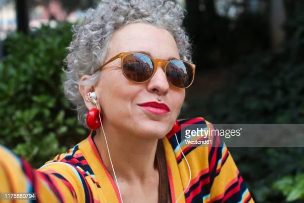 portrait of pierced mature woman wearing sunglasses and earphones - unkonventionell stock-fotos und bilder