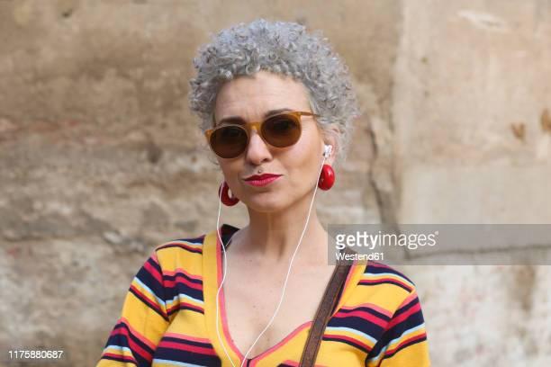 portrait of pierced mature woman with ear phones - young at heart woman fotografías e imágenes de stock