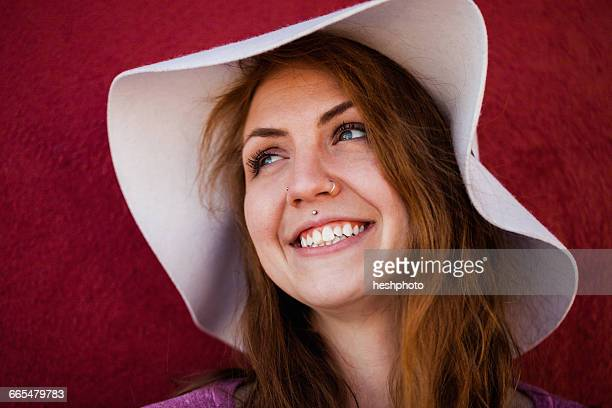 portrait of pierced woman wearing sunhat looking away smiling - heshphoto stock pictures, royalty-free photos & images