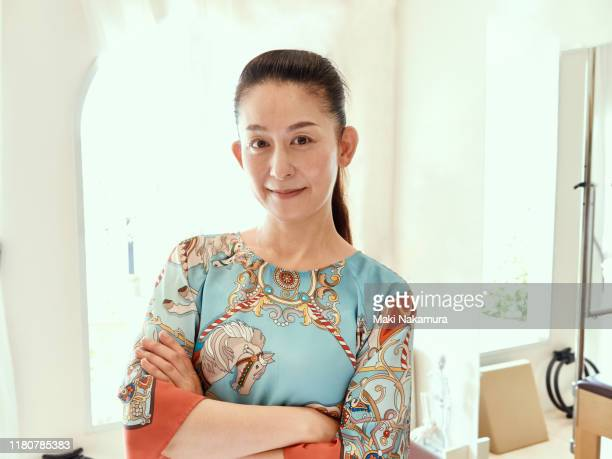 portrait of pilates studio owner standing with arms folded - maebashi city stock photos and pictures