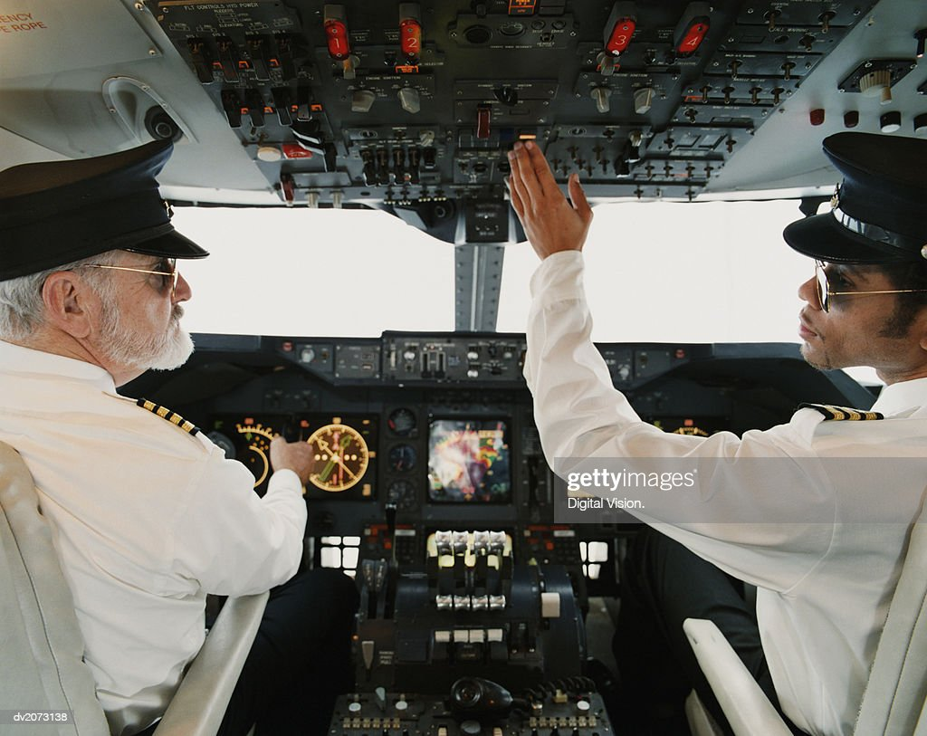 Portrait of Pilots Sitting in the Cockpit, Adjusting the Controls : Stock Photo