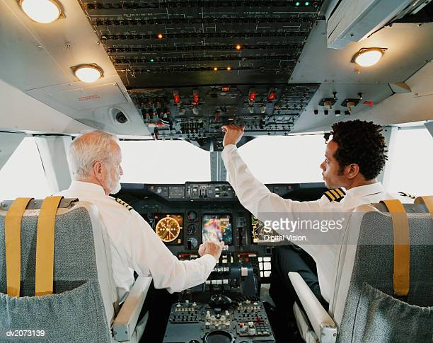 portrait of pilots sitting in the cockpit, adjusting the controls - piloting stock pictures, royalty-free photos & images