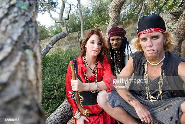 portrait of pirates sitting under trees with woman pirate holding a gun - pirates headshots stock pictures, royalty-free photos & images