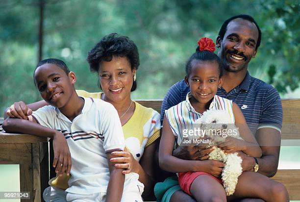 Portrait of Pittsburgh Steeler great John Stallworth with his wife and two children taken at their home in Huntsville Alabama 1986 His daughter...