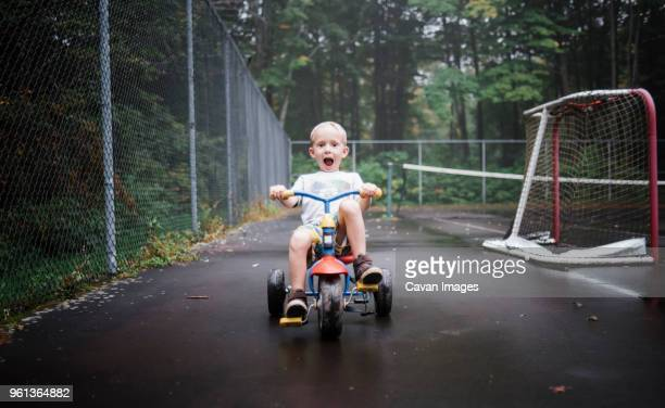 portrait of playful boy riding tricycle at playground - tricycle stock pictures, royalty-free photos & images
