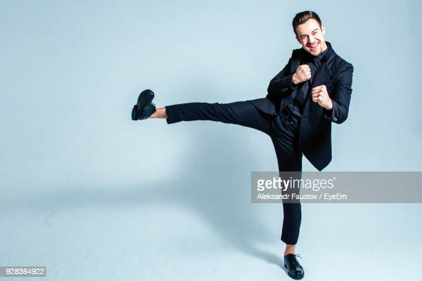portrait of playful businessman with legs apart standing against white background - benen gespreid stockfoto's en -beelden