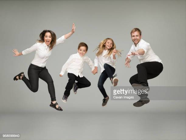 portrait of playful family jumping against gray background - 隣り合わせ ストックフォトと画像