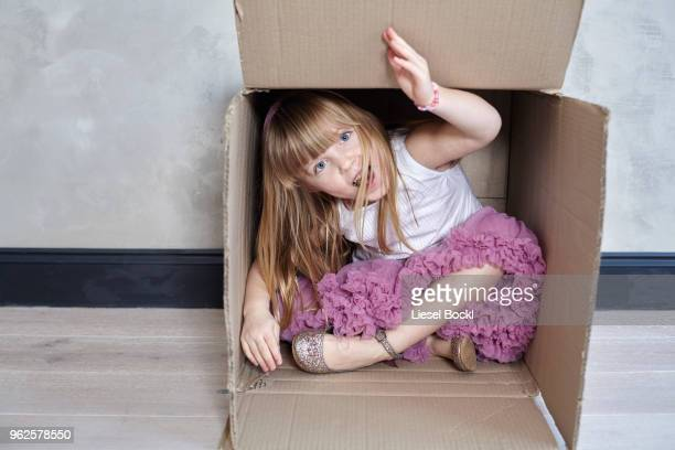 portrait of playful girl sitting in box against wall - little girls up skirt stock pictures, royalty-free photos & images