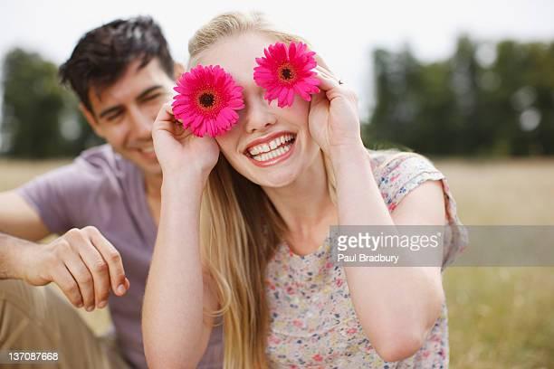 Porträt von lustige Frau holding Blumen über Augen