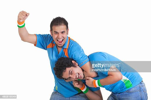 Portrait of playful young male friends in jerseys isolated over white background