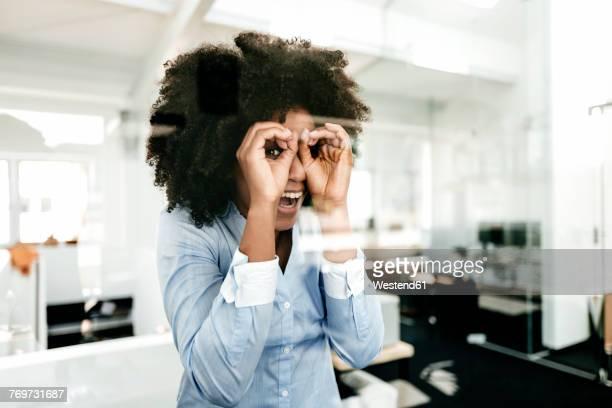 portrait of playful young woman in office - blickwinkel der aufnahme stock-fotos und bilder
