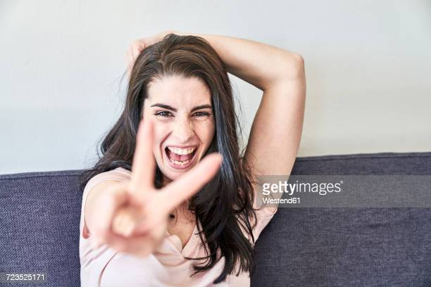 Portrait of playful young woman making victory sign