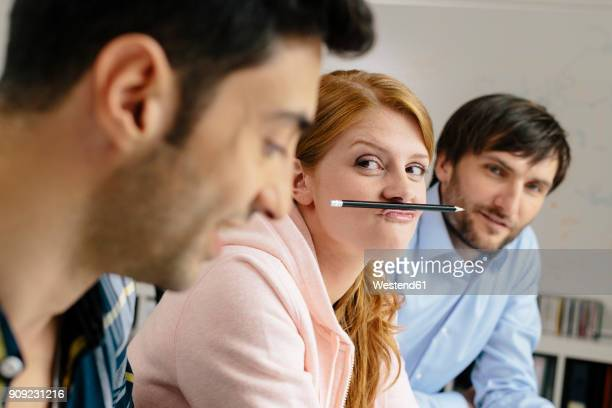 portrait of playful young woman with colleagues in office - spaß stock-fotos und bilder