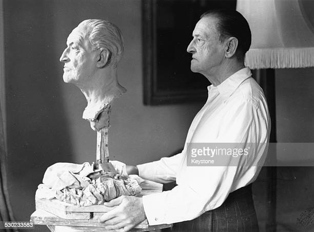 Portrait of playwright and novelist Somerset Maugham posing with a bust in his likeness at the Dorchester Hotel London December 14th 1948