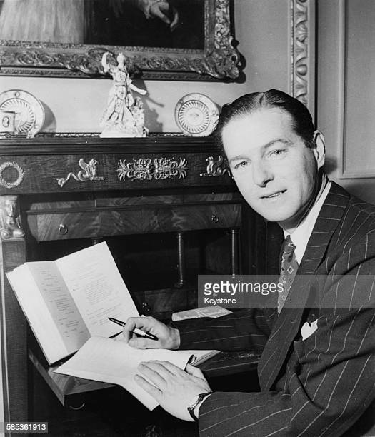 Portrait of playwright Terence Rattigan writing at his desk, 1948.
