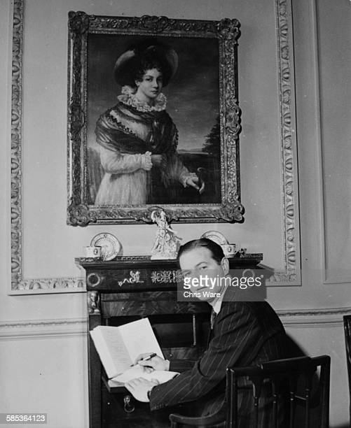 Portrait of playwright Terence Rattigan writing at his desk, sitting below a portrait of author Jane Austen, 1948.