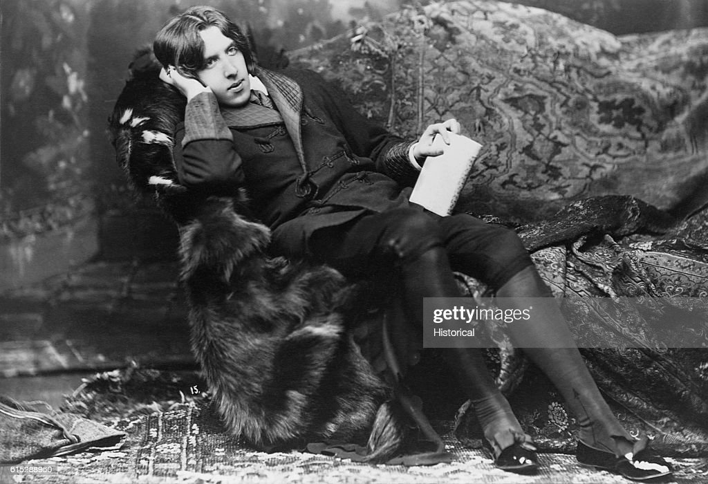 A portrait of poet and novelist, Oscar Wilde, (1854-1900), known for his languid poses and typical costume including a velvet robe and black silk stockings. Wilde was popular for his wit and satire of Victorian society, which was apparent in his work The Importance of Being Earnest.