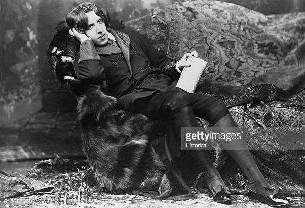 A portrait of poet and novelist Oscar Wilde known for his languid poses and typical costume including a velvet robe and black silk stockings Wilde...
