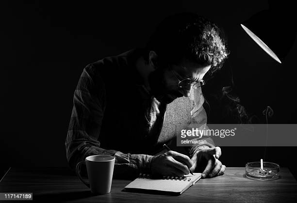 portrait of poet writing on table in the dark - authors stockfoto's en -beelden