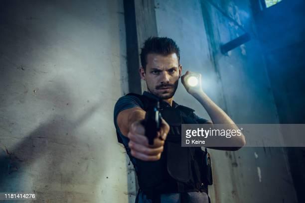 放棄された建物の中を歩く警官の肖像画 - 犯罪捜査 ストックフォトと画像