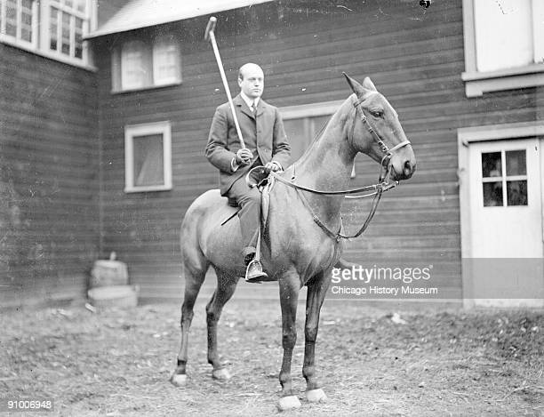 Portrait of polo player holding a polo mallet sitting on horseback in a paddock area in front of a barn in Chicago Illinois 1901 From the Chicago...
