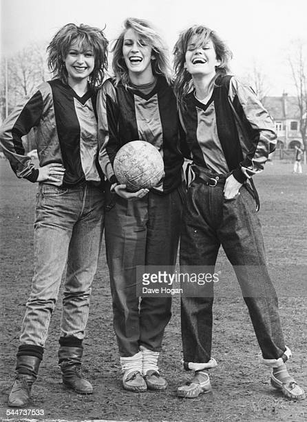 Portrait of pop band 'Bananarama', Keren Woodward, Sarah Dallin and Siobhan Fahey, wearing football shirts and standing in a field, March 16th 1983.