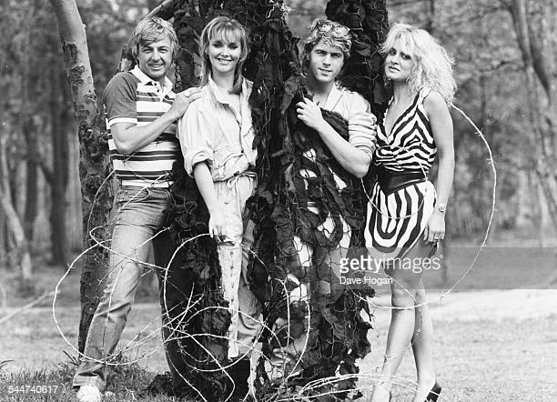 Portrait of pop group 'Bucks Fizz' Bobby G Cheryl Baker Mike Nolan and Jay Aston wrapped in camouflage netting and barbed wire circa 1985