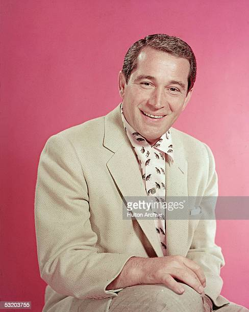 Portrait of popular American singer Perry Como as he sits in a pink and black shirt under a light tan jacket, mid 1950s.