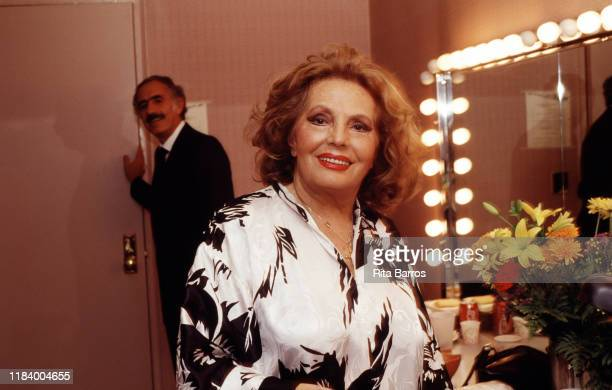 Portrait of Portuguese Fado singer Amalia Rodrigues as she sits backstage at Town Hall New York New York November 2 1990 Behind her is record label...