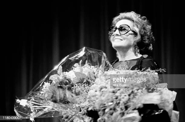 Portrait of Portuguese Fado singer and actress Amalia Rodrigues holds a bouquet of flowers on stage during a retrospective of her films at the...