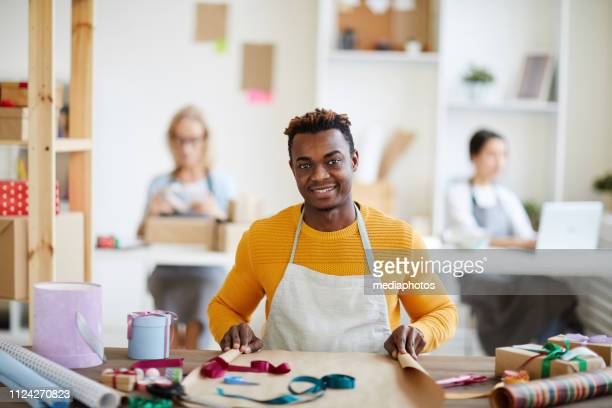 Portrait of positive handsome young African craftsman in apron sitting at table and wrapping gifts in workshop