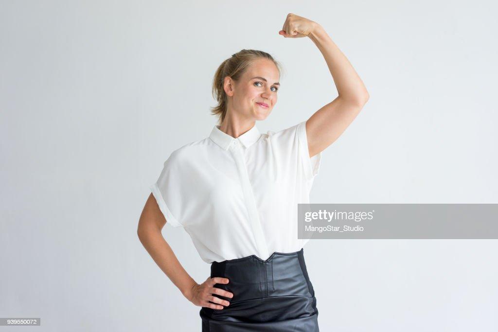 Portrait of positive young woman showing bicep : Foto de stock