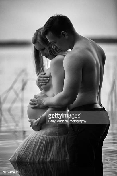 portrait of pregnant couple standing in a lake - weibliche brust schwanger stock-fotos und bilder