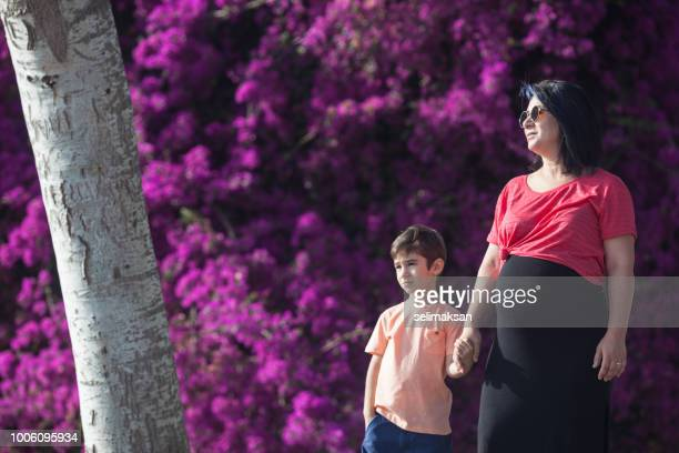 Portrait Of Pregnant Mother And Her Son In Front Of Purple Bougainvillea Flowers