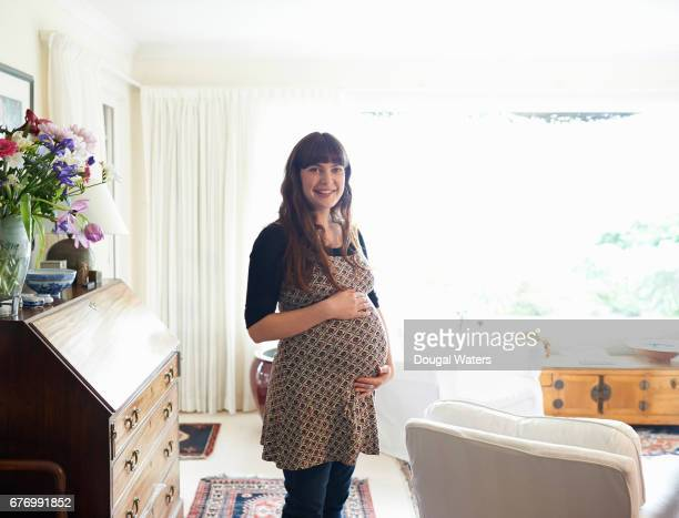 Portrait of pregnant woman at home with hands holding stomach.
