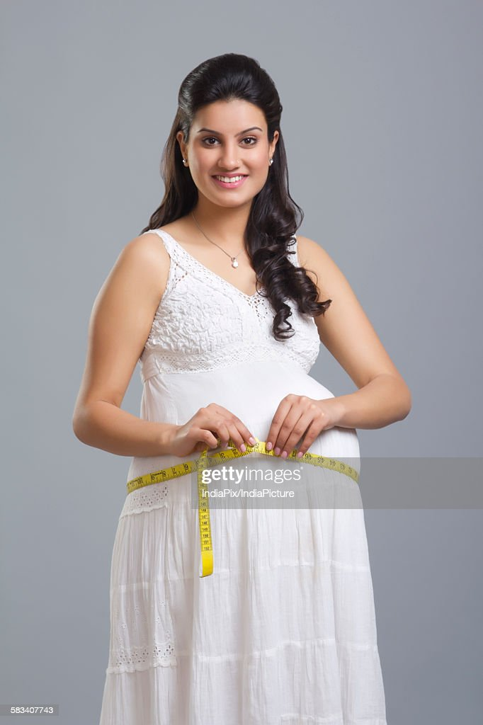 Portrait of pregnant woman measuring her stomach : Stock Photo
