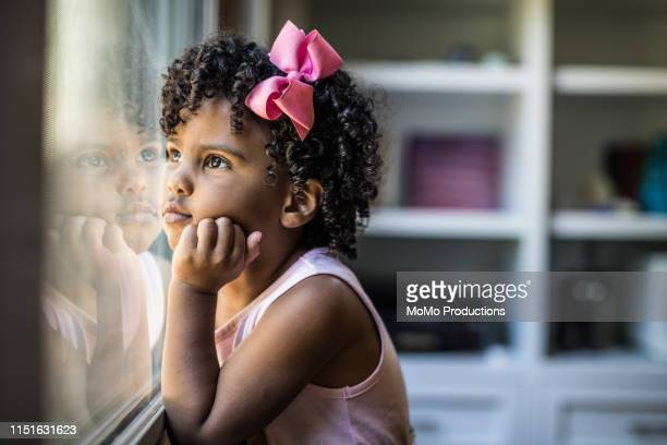 Portrait of preschool age girl looking out window