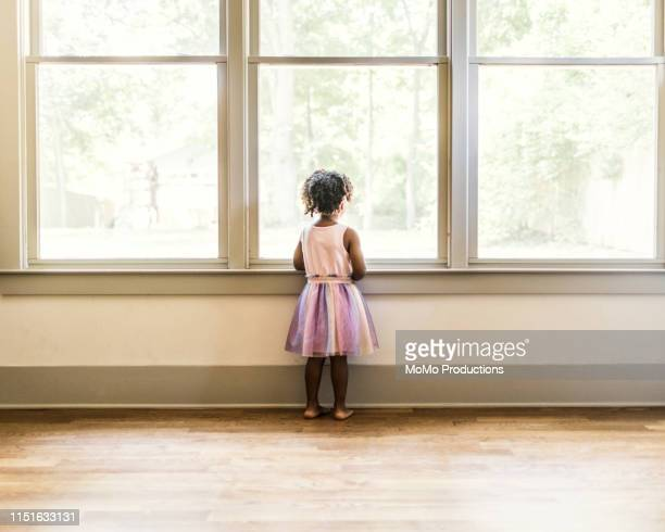 portrait of preschool age girl looking out window - rear view stock pictures, royalty-free photos & images