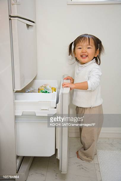 Portrait of preschool age girl opening freezer drawer at home