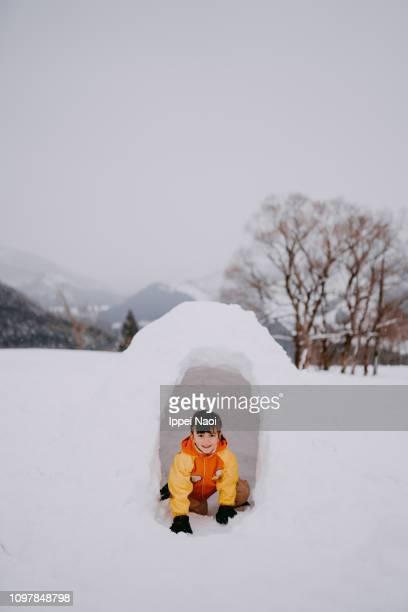 Portrait of preschool girl smiling at camera in igloo in snowy mountains