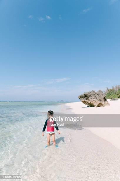 Portrait of preschool girl standing in shallow tropical water, Okinawa, Japan