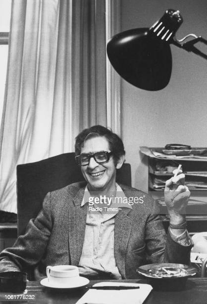 Portrait of presenter Denis Norden smoking a cigarette at his desk September 4th 1972