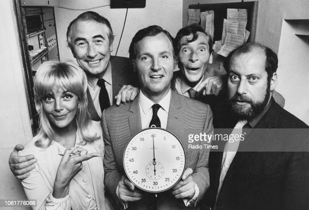 Portrait of presenter Nicholas Parsons holding a large stop watch photographed with his guests Aimi McDonald Peter Jones Kenneth Williams and Clement...