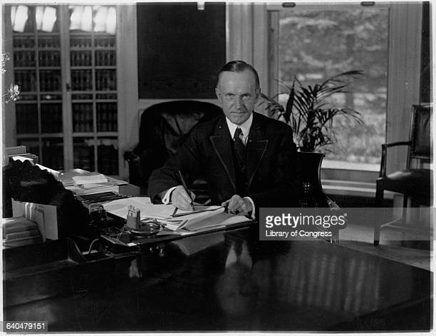 A portrait of President Calvin Coolidge sitting at his desk in the Oval office as he signs a tax bill Washington DC August 15 1923